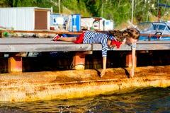 Deux filles s'asseyant sur le dock Image libre de droits