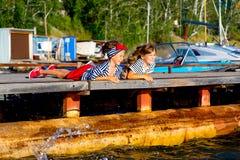 Deux filles s'asseyant sur le dock Photo libre de droits