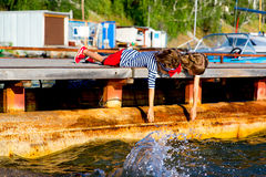 Deux filles s'asseyant sur le dock Photo stock