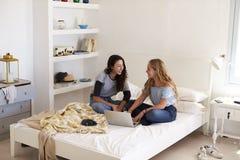 Deux filles s'asseyant sur le lit utilisant l'ordinateur portable regardant l'un l'autre Photos stock
