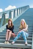 Deux filles s'asseyant sur le pont en métal Image stock