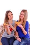 Deux filles s'asseyant sur un sofa et mangeant de la pizza Image libre de droits