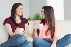 Deux filles s'asseyant sur un sofa se regardant et buvant un être Image stock