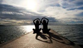 Deux filles s'asseyent avec les mains en forme de coeur Image libre de droits