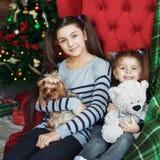 Deux filles s'asseyent avec un chien sur le divan Le concept de Noël photographie stock libre de droits