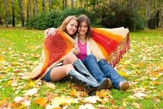 Deux filles s'asseyent en stationnement d'automne Photographie stock libre de droits
