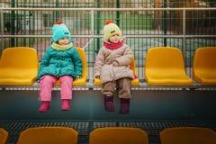 Deux filles s'asseyent sur une tribune Photographie stock