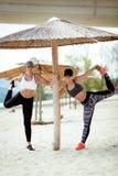 Deux filles s'exerçant sur la plage Photo stock