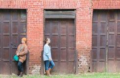 Deux filles se penchant sur le mur de briques Image stock