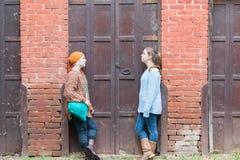 Deux filles se penchant sur le mur de briques Image libre de droits