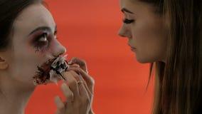 Deux filles se préparent à une partie des forces foncées Maquillage pour Halloween ou tout le jour de saints L'artiste de maquill banque de vidéos