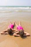 Deux filles se situent sur votre dos sur la plage sablonneuse à mi-chemin dans le wate Photo libre de droits