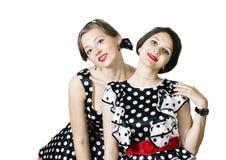 Deux filles se sont habillées dans le style de la goupille- posant sur un fond blanc Photos stock