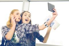 Deux filles se tiennent avec des valises à l'aéroport et regarder le comprimé Un voyage avec des amis Photographie stock libre de droits