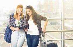 Deux filles se tiennent avec des valises à l'aéroport et regarder le comprimé Un voyage avec des amis Image stock