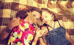 Deux filles se trouvant sur l'herbe Photographie stock libre de droits