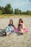 Deux filles se trouvant sur la plage et le sourire Photo libre de droits