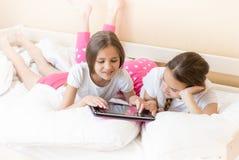 Deux filles se trouvant sur le lit et la vidéo de observation sur la tablette Images libres de droits