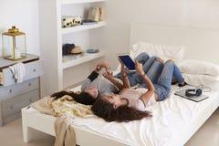 Deux filles se trouvant sur le lit utilisant le téléphone et le comprimé, vue élevée photo stock