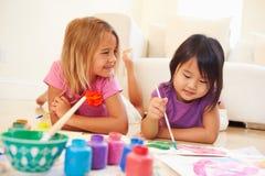 Deux filles se trouvant sur le plancher et la photo de peinture à la maison Photos stock