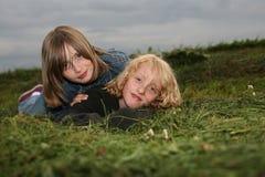 Deux filles se trouvant sur le pré photo stock