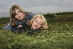 Deux filles se trouvant sur le pré photographie stock