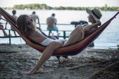 Deux filles se trouvant sur un salon à la plage en été Photo stock