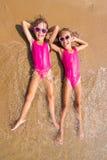 Deux filles se trouvent sur son dos sur le ressac de la plage sablonneuse de mer Photos libres de droits