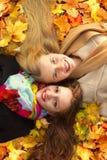 Deux filles se trouvent sur une feuille en parc d'automne Photographie stock