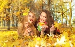 Deux filles se trouvent sur une feuille en parc d'automne Image libre de droits