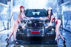 Deux filles sexy dans le lavage de voiture photographie stock libre de droits