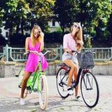Deux filles sexy sur bicyclettes Verticale extérieure de mode Image libre de droits
