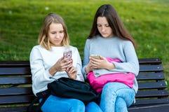 Deux filles sont des étudiantes En été ils se reposent sur le banc en nature Dans des mains de tenir des smartphones s'affiche images stock