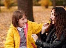 Deux filles sont en parc de ville d'automne Ils parlent et rient image libre de droits