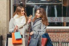 Deux filles sont heureuses avec une carte de crédit devant des WI de showwindow Photographie stock
