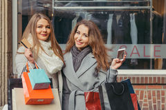 Deux filles sont heureuses avec une carte de crédit devant l'exposition-fenêtre avec la vente écrite là-dessus Photo stock