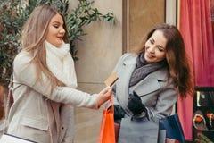 Deux filles sont heureuses avec une carte de crédit par les achats Photos stock