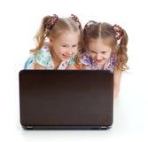 Deux filles sont souriantes et regardantes l'ordinateur portatif Photos libres de droits