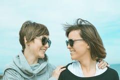 Deux filles souriant et ayant l'amusement sur la plage Mode de vie sain et gai Photo stock
