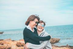 Deux filles souriant et ayant l'amusement sur la plage Mode de vie sain et gai Image stock