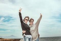 Deux filles souriant et ayant l'amusement sur la plage Mode de vie sain et gai Photographie stock
