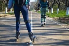 Deux filles sur des patins de rouleau montent le long de la route l'un à côté de l'autre Images libres de droits