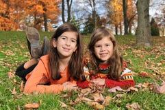 Deux filles sur l'herbe pendant l'automne Images libres de droits
