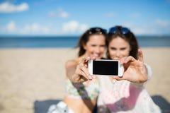 Deux filles sur la plage prenant le selfie par le smartphone Image stock
