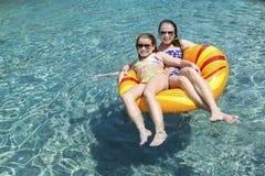Deux filles sur le flotteur dans la piscine image stock
