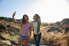 Deux filles sur un ourpost rocheux Photographie stock libre de droits