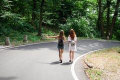 Deux filles sur un voyage par la route faisant de l'auto-stop Images libres de droits
