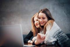 Deux filles surfant le filet, le signalant sur les réseaux sociaux sur un ordinateur portable et ayant l'amusement Photo stock