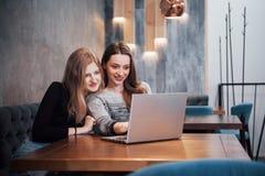 Deux filles surfant le filet, le signalant sur les réseaux sociaux sur un ordinateur portable et ayant l'amusement Image stock