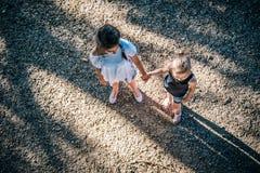 Deux filles tenant des mains sur le terrain de jeu Photographie stock libre de droits